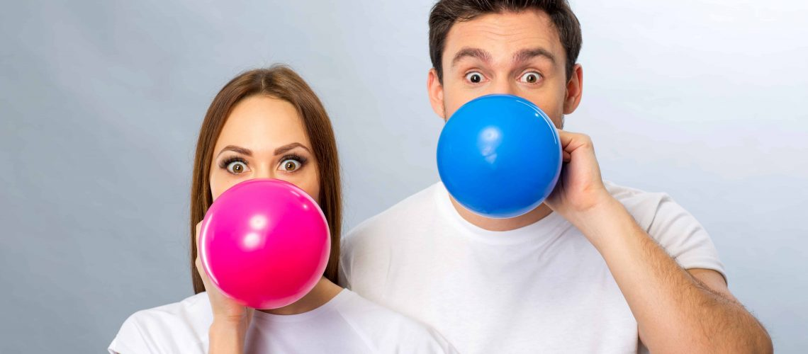 Brighten your life. Cheerful pleasant young couple blowing balloons and having fun while standing isolated on grey background