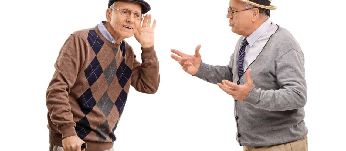 Senior man struggling to hear a friend in a discussion isolated on white background